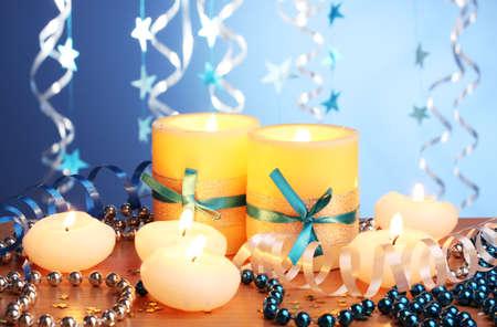 Beautiful candles, gifts and decor on wooden table on blue background Stock Photo - 13052967