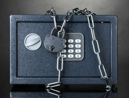 safe with chain and lock on grey background Stock Photo - 13052992