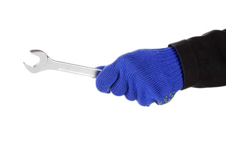 Wrench in hand with protection glove isolated on white photo
