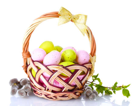 basket with Easter eggs and pussy-willow twigs isolated on white photo