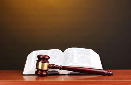 judgements: Judges gavel and open book on wooden table on brown background