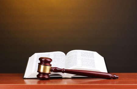 jurado: Libro de martillo y de c�digo abierto del juez en la mesa de madera sobre fondo marr�n