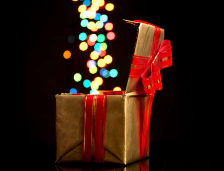 open golden gift box with bokeh background on black photo