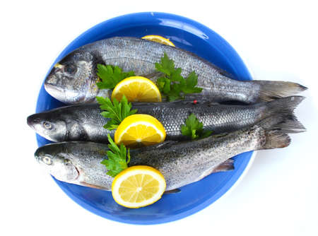 Fresh fishes with lemon and parsley on plate isolated on white photo