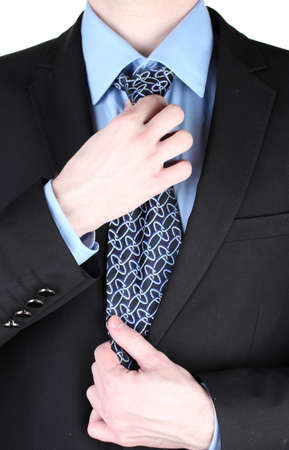 coat and tie: businessman correcting a tie close up