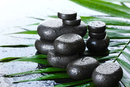 Spa stones with drops on green palm leaf on grey background Stock Photo - 13061758