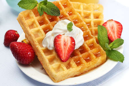 waffles: belgium waffles with honey, strawberries and mint on plate isolated on white