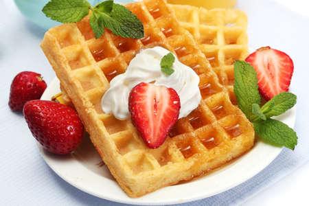 waffles: gofres belgas con miel, las fresas y la menta en un plato aislado en blanco Foto de archivo