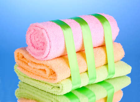 Colorful towels with ribbon on blue background Stock Photo - 13061759