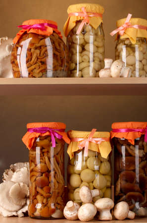 shelfs: delicious marinated mushrooms in the glass jars, raw champignons and oyster mushrooms on wooden shelfs