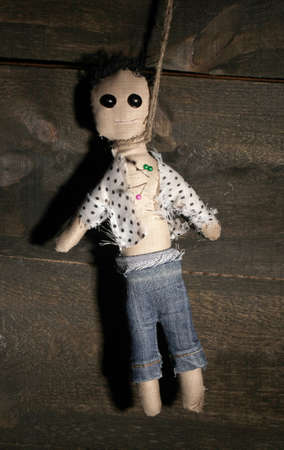 Hanged doll voodoo boy on wooden background photo