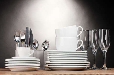 Clean plates, glasses, cups and cutlery on wooden table on grey background Stock Photo - 13100133