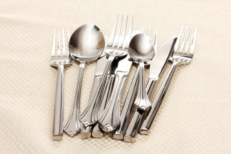 Forks, spoons and knives on a beige tablecloth photo