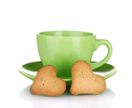 Green cup and saucer with heart-shaped cookies isolated on white photo