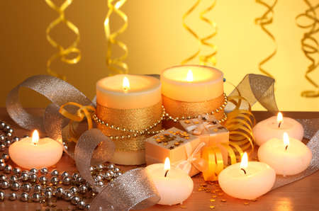 Beautiful candles, gifts and decor on wooden table on yellow background Stock Photo - 13100141