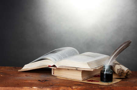 old books, scrolls, feather pen and inkwell on wooden table on grey background photo