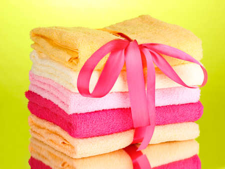 Colorful towels with ribbon on green background Stock Photo - 13099310