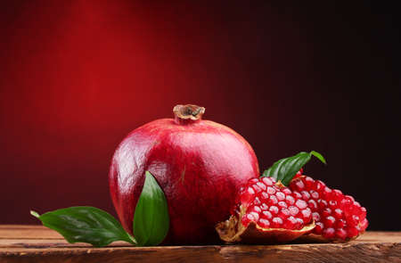 pomegranates: ripe pomegranate fruit with leaves on wooden table on red background