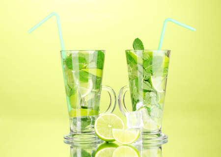 Glasses of cocktail with lime and mint on green background photo