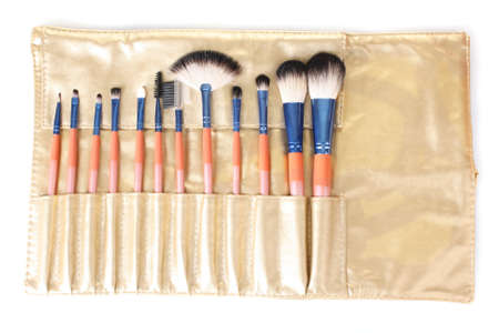 Set of make-up brushes in golden leather case isolated on white photo