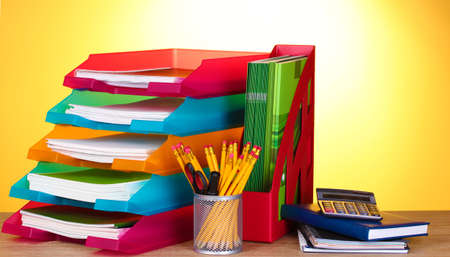 secretary tray: bright paper trays and stationery on wooden table on yellow background