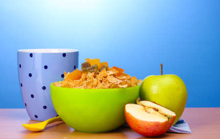tasty cornflakes in green bowl, apples and glass of milk on wooden table on blue background Stock Photo - 13163102