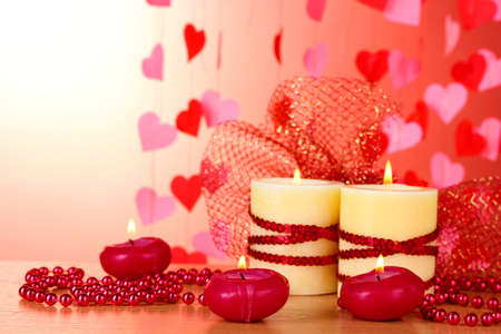 Beautiful candles with romantic decor on a wooden table on a red background Stock Photo - 13163214