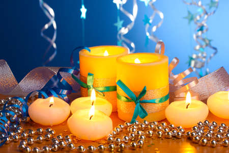 Beautiful candles, gifts and decor on wooden table on blue background Stock Photo - 13163460