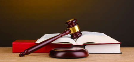 defendant: Judges gavel and books on wooden table on brown background