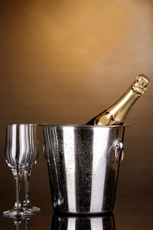 gold capped: Bottle of champagne in bucket and goblets on brown background