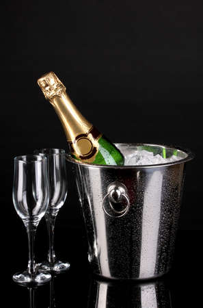 Bottle of champagne in bucket isolated on black photo