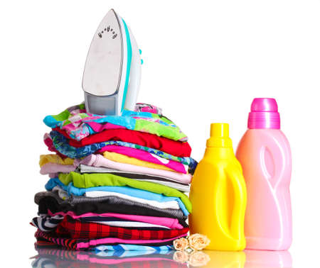 Pile of colorful clothes and electric iron with detergent isolated on white photo