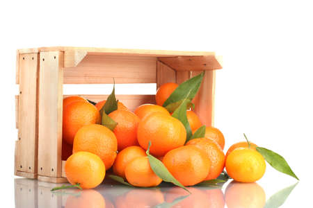 mandarin orange: Ripe tasty tangerines with leaves in wooden box dropped isolated on white Stock Photo