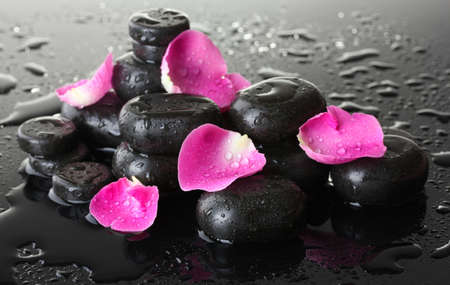 Spa stones with drops and rose petals on grey background Stock Photo - 13163266