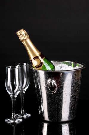 Bottiglia di champagne nel secchio isolato su fondo nero Archivio Fotografico