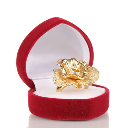 Gold ring with golden flower and clear crystals in red velvet box isolated on white photo