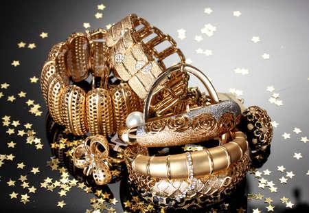 Mooie gouden sieraden op een grijze achtergrond Stockfoto