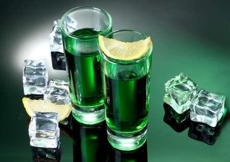 ajenjo: Dos vasos de absenta, lim�n y hielo sobre fondo verde