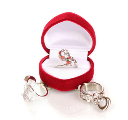 Silver ring with red, pink and clear crystals in red velvet box and some silver rings isolated on white photo