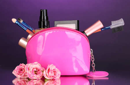 Make up bag with cosmetics and brushes on violet background Stock Photo - 13213791