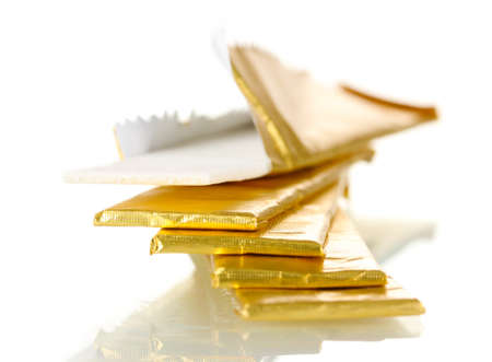 chewing gums wrapped in golden foil, isolated on white photo