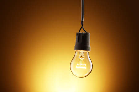 lit lamp: A lit light bulb on yellow background Stock Photo