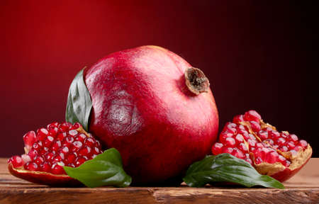 ripe pomegranate fruit with leaves on wooden table on red background Stock Photo - 13234159