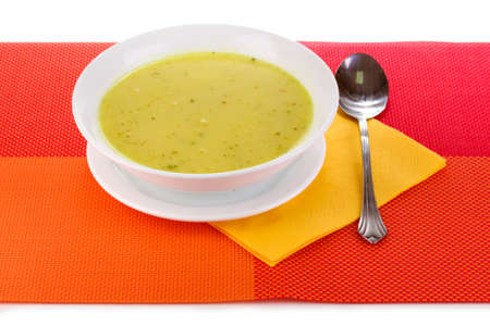 Tasty soup on red tablecloth isolated on white photo