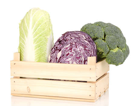 Сabbages and broccoli in wooden crate isolated on white photo