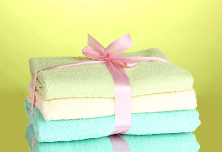Colorful towels with ribbon on green background Stock Photo - 13234236