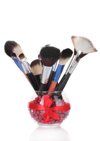 make-up brushes in glass vase isolated on white Stock Photo - 13234383