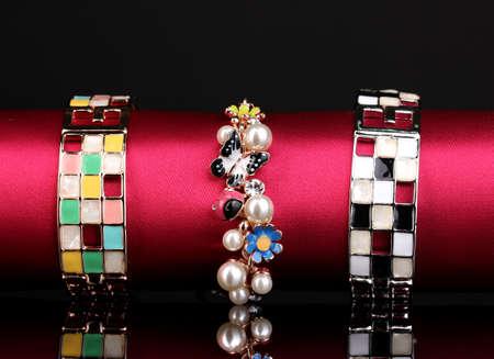 Three fashion bracelets on the pink cloth on black background Stock Photo - 13234210