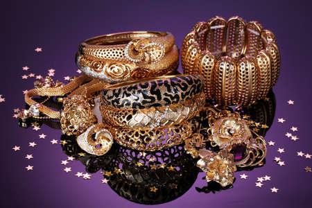 Beautiful golden jewelry on purple background photo
