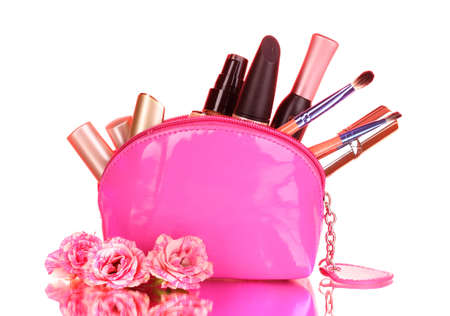 Make up bag with cosmetics and brushes on pink background photo